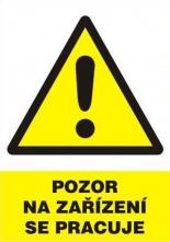 """Tabulka """"Pozor na zařízení se pracuje"""" plastová rozměr 210 x 297 mm symbol trojúhelníku s vykřičníkem žluto/bílo/černá"""